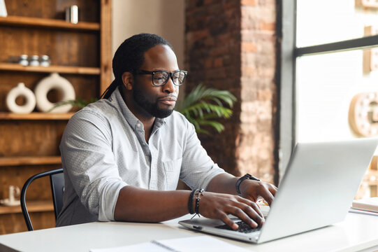 Busy bored young African-American male author office worker in glasses sitting at the desk typing on laptop, working on project, writing creating article or blog, feeling lack of motivation to finish