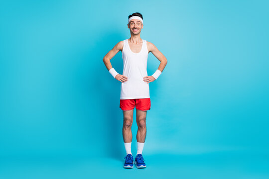 Full length photo of sporty man hold hand waist wear white singlet gumshoes isolated over blue color background