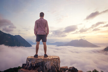 Man standing on a mountain top above the clouds Wall mural