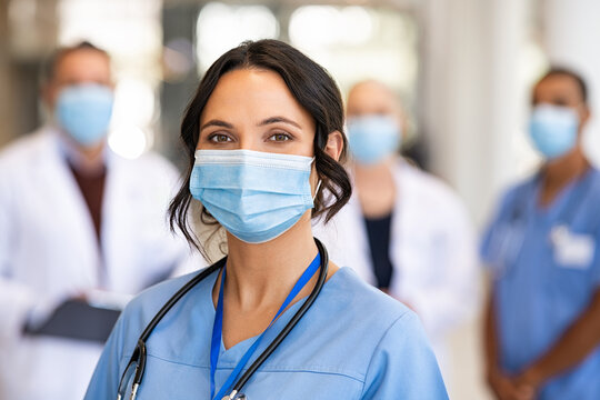 Happy nurse with face mask smiling at hospital