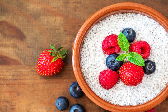 Chia seed pudding made with fresh berries on wooden table.  Chia seeds Yogurt..