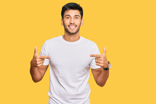 Young handsome man wearing casual white tshirt looking confident with smile on face, pointing oneself with fingers proud and happy.