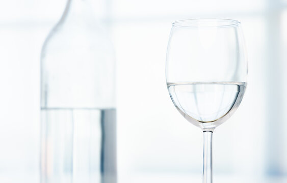 A glass of water and a clear glass water bottle are placed on the table in the house on a white background.