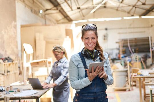 Handwerker Frau in Werkstatt mit Tablet Computer