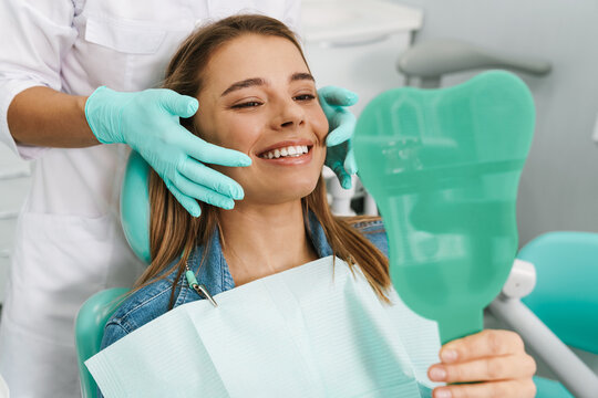 European young woman smiling while looking at mirror in dental clinic