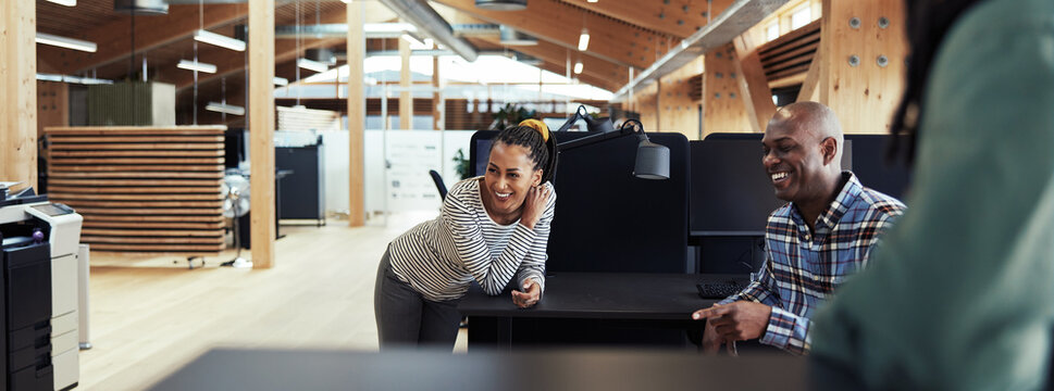 Group of young African American businesspeople laughing together during a casual meeting in a modern office.