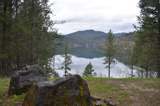 View of the Whiskeytown Lake reservoir glassy water with trees and boulders in the foreground
