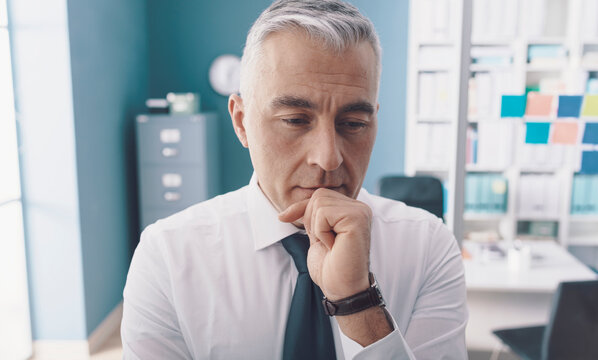 Pensive businessman thinking with hand on chin
