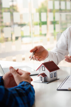The real estate agent is explaining the house style to the clients who come to contact to see the house design and the purchase agreement, Mortgage loan approval home loan and insurance concept.