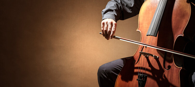 Cello player or cellist performing in an orchestra background