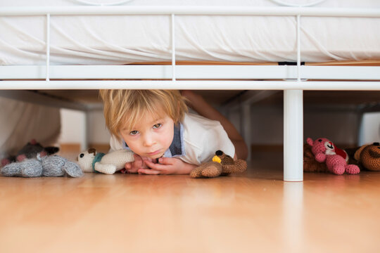 Little toddler child, hiding under the bed with stuffed toys, scared