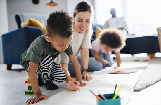 Multi ethnic family with two small children drawing pictures, home office.