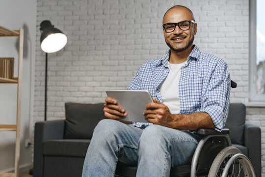 Disabled young african american man sitting in wheelchair and using digital tablet