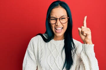 Beautiful hispanic woman wearing casual sweater and glasses pointing finger up with successful idea. exited and happy. number one. Wall mural