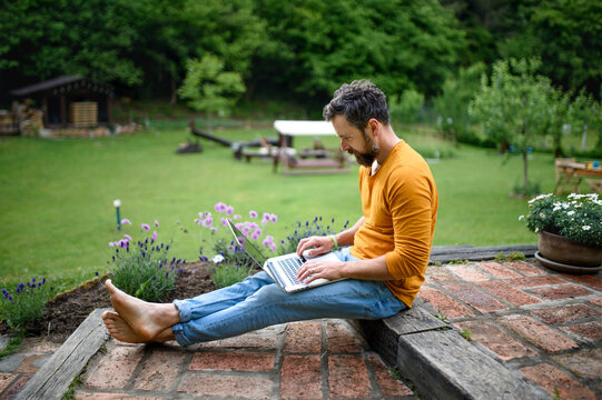 Mature man with laptop working outdoors in garden, green home office concept.