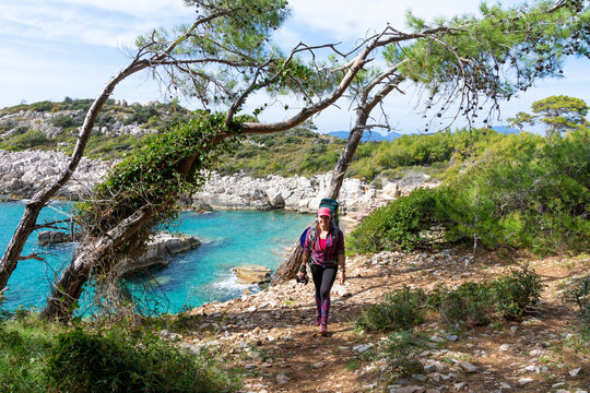 Smiling girl in a pink shirt and hat moves with a backpack on the Leah Trail. Trail along the Mediterranean coast.