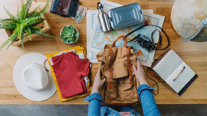 Fototapeta Top view of young woman packing for vacation trip holiday, desktop travel concept. obraz