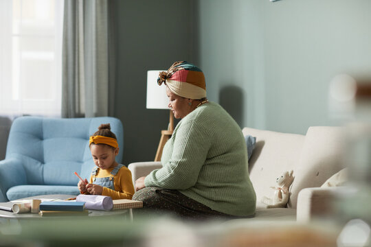 Side view portrait of mature African-American woman drawing with cute little girl in minimal home interior, copy space