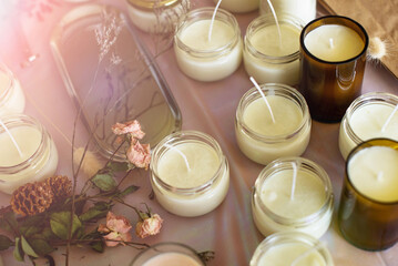 Fototapeta Soy Candles poured into recycled bottles and jars. Many soy wax candles together on store or workshop background. . Ecological and vegan business. obraz