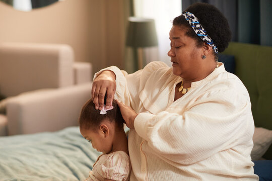 Side view portrait of African-American grandmother combing hair of cute little girl while sitting on bed in cozy home interior