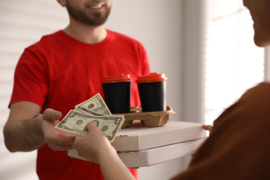 Deliveryman receiving tips from woman indoors, closeup