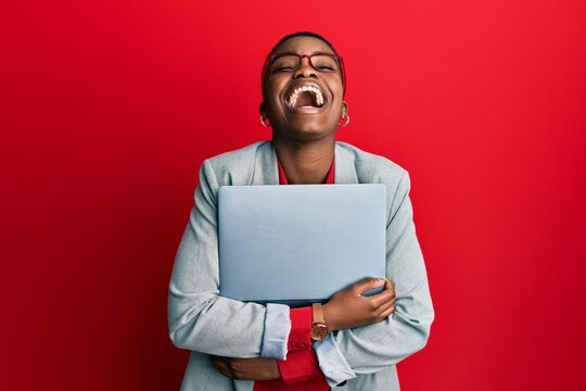 Young african american businesswoman holding laptop smiling and laughing hard out loud because funny crazy joke.