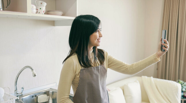 Young Asia woman use mobile phone for conference video call in kitchen pantry at home