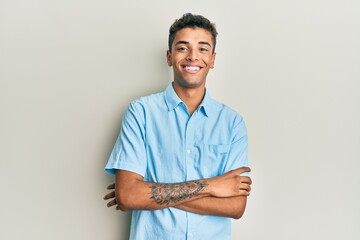 Fototapeta Young handsome african american man wearing casual clothes happy face smiling with crossed arms looking at the camera. positive person.