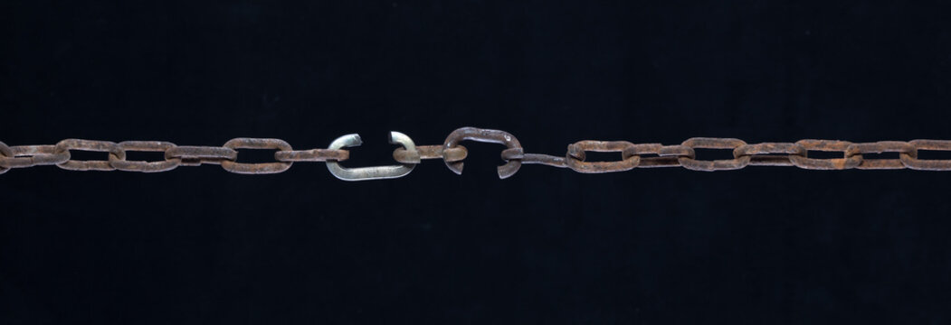 broken link metal chain isolated on black background