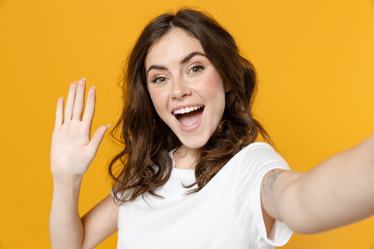 Close up young excited smiling friendly cool caucasian woman 20s in white basic casual tshirt do selfie shot on mobile phone waving hands say hello isolated on yellow color background studio portrait