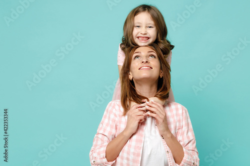Happy woman in pink clothes have fun with cute child baby girl 5-6 years old Mommy little kid daughter stand behind hug isolated on pastel blue azure background studio Mothers Day love family concept