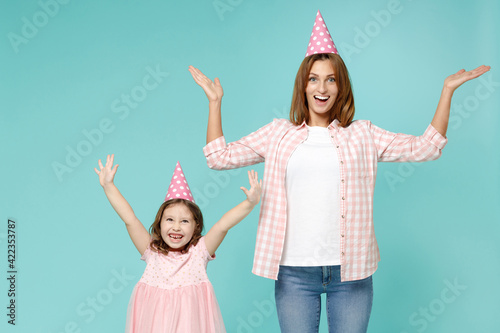 Happy woman in pink clothes birthday hat have fun child baby girl 5-6 years old. Mom little kid daughter raised up hands celebrate isolated on blue background studio. Mother's Day love family concept.