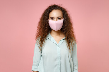 Young black african curly woman 20s wearing blue shirt reusable face mask to safe from coronavirus...