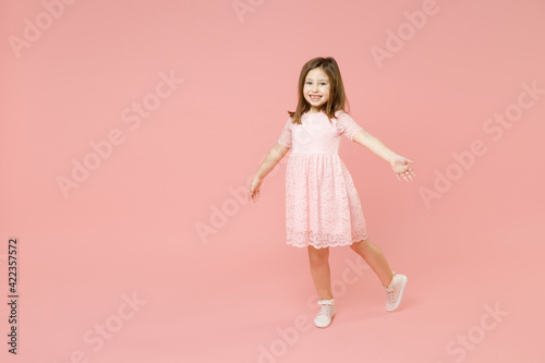 Full body length little cute kid girl 5-6 years old wears rosy dress have fun walk go step isolated on pastel pink background child studio portrait. Mother's Day love family people lifestyle concept.