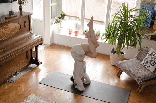 A young woman practicing yoga at home.