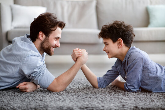 Happy father competing in arm-wrestling with his son, enjoying time together at home, side view