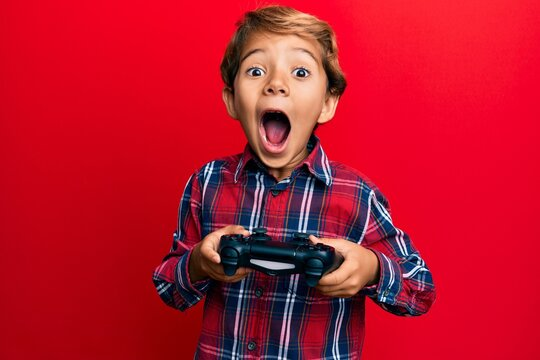 Adorable latin kid playing video game holding controller afraid and shocked with surprise and amazed expression, fear and excited face.