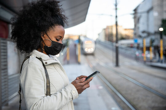 Young woman in the evening at sunset in city wears protective face mask during the global pandemic from Covid-19 Coronavirus looks at the smartphone while waiting for the tram to go home after work