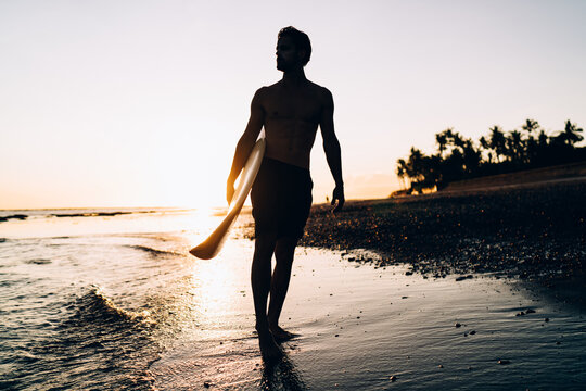 Silhouette of male spending evening for surfing during summer twilight at Carribean sea, amateur man with professional surfboard recreating with sportive activity in Thailand visiting Phuket beach