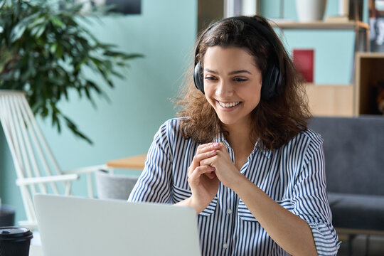 Happy latin hispanic girl college student wearing headphones watching distance online class, remote university webinar or having talk on laptop video conference call virtual meeting at home or campus.