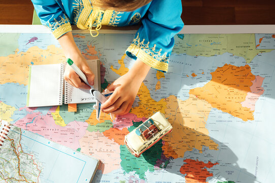 happy boy with blue djellaba takes notes in notebook next to world map