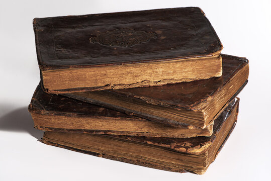 Stack of old worn out leather-bound books isolated on white background. Closeup.