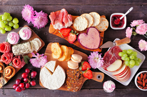 Mother's Day theme charcuterie table scene against a dark wood background. Assorted cheese, meat, fruit and sweet appetizers. Top down view.