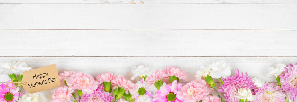 Happy Mothers Day gift tag with long bottom border of pink and white flowers. Top view on a white wood banner background. Copy space.