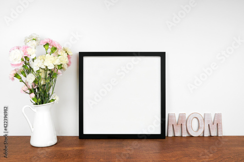 Mock up black frame with vase of carnation flowers and wooden MOM letters. Mother's Day decor theme. Wood shelf against a white wall. Copy space.