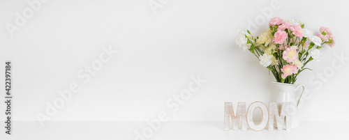 Mother's Day decor with vase of carnation flowers and wooden MOM letters on a white shelf against a white wall banner background. Copy space.