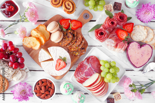 Mother's Day theme charcuterie table scene against a white wood background. Variety of cheeses, meats, fruit and sweets. Top view.