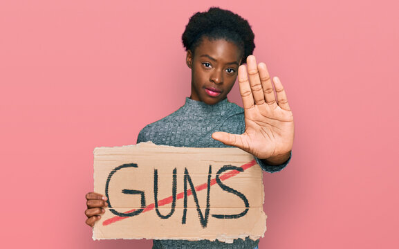 Young african american girl holding no guns warning banner with open hand doing stop sign with serious and confident expression, defense gesture