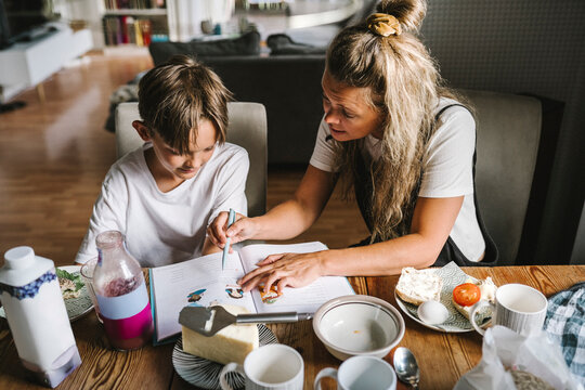 Mother teaching son while having breakfast in living room