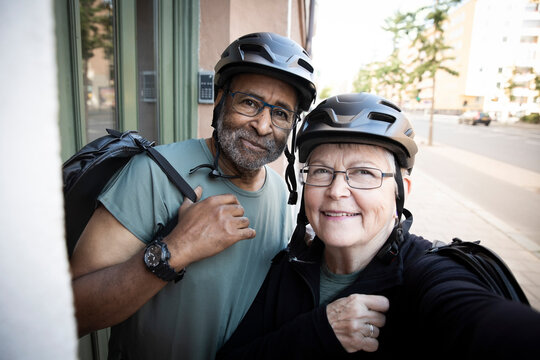 Smiling senior couple taking selfie with cycling helmet outside house